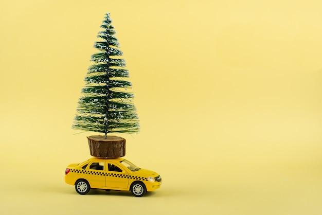 Taxi miniatura giallo che trasporta un albero di natale