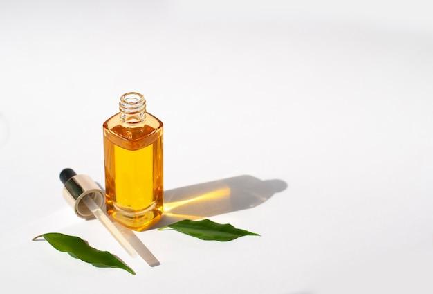 Olio cosmetico mock-up giallo su sfondo bianco con foglie verdi e spazio di copia