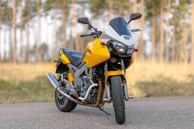 Motocicletta gialla su strada nella zona della foresta, vista frontale