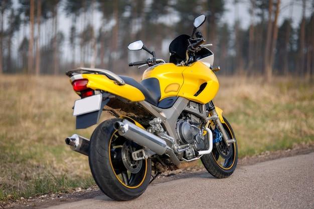 Motocicletta gialla su strada nella zona della foresta, vista posteriore