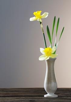 Narciso giallo in vaso sul tavolo di legno su sfondo scuro