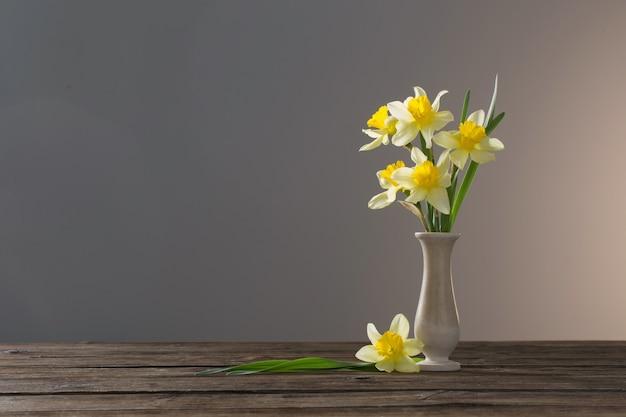 Narciso giallo in vaso sulla tavola di legno sulla superficie scura