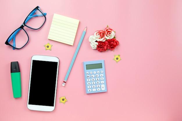 Calcolatore giallo del telefono cellulare del taccuino e vetri blu dell'indicatore di hilight su stile pastello del fondo rosa con il percorso di ritaglio del flatlay del copyspace sul moblie dello schermo
