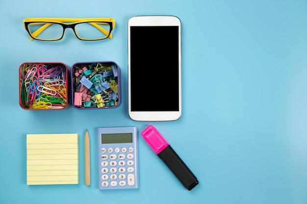 Calcolatore giallo del telefono cellulare del taccuino e clip di vetro dell'indicatore di hilight su stile pastello del fondo blu con il percorso di ritaglio del flatlay del copyspace sul moblie dello schermo