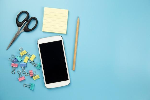 Calcolatore giallo di forbici del telefono cellulare del taccuino e su stile pastello del fondo blu con il percorso di ritaglio del flatlay del copyspace sul moblie dello schermo