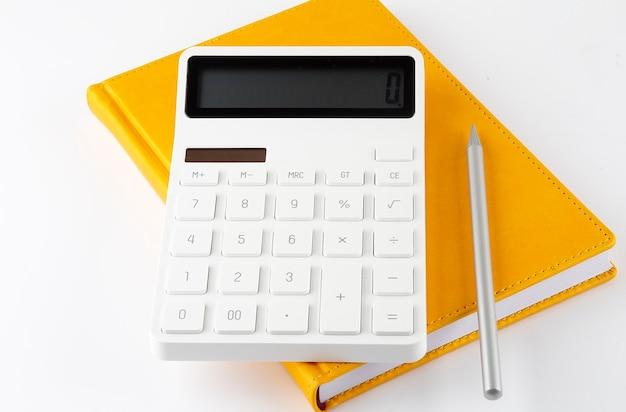 Taccuino giallo con una matita e una calcolatrice su sfondo bianco