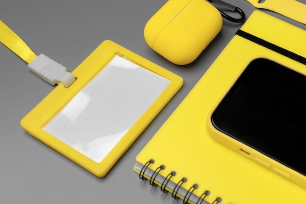 Blocco note giallo, smartphone e auricolari su sfondo grigio, copia dello spazio
