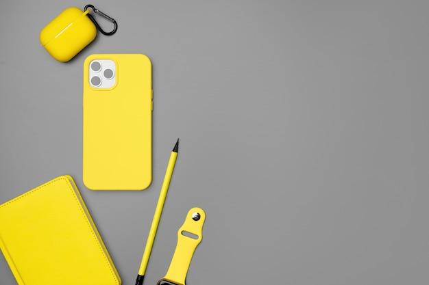 Blocco note, smartphone e auricolari gialli su gray