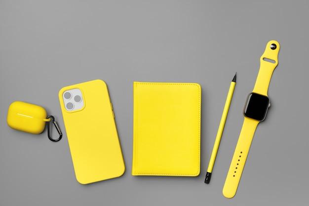 Blocco note giallo con smartphone, smartwatch e auricolari su vista dall'alto grigio