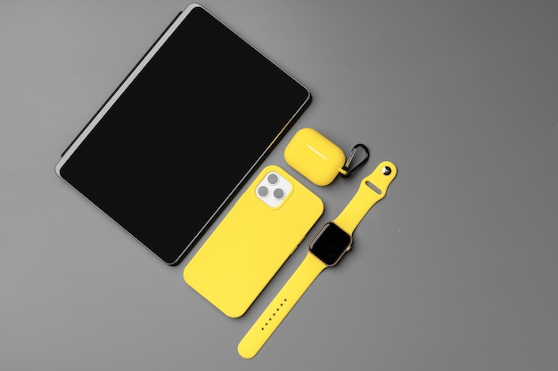 Blocco note giallo con smartphone, smartwatch e auricolari su grigio