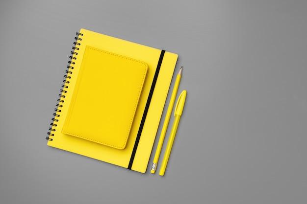 Blocco note giallo con matita gialla su sfondo grigio vicino