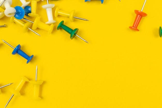 Scrivania da ufficio gialla con un sacco di puntine colorate, bordo di cancelleria per materiale scolastico, composizione norder con foto spazio copia