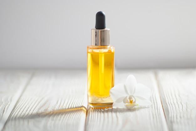 Olio giallo nella bottiglia di vetro con fiore di orchidea e asciugamano bianco