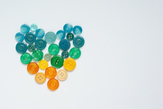 Bottoni da cucire gialli, arancioni, verdi e blu a forma di cuore su superficie bianca monocromatica