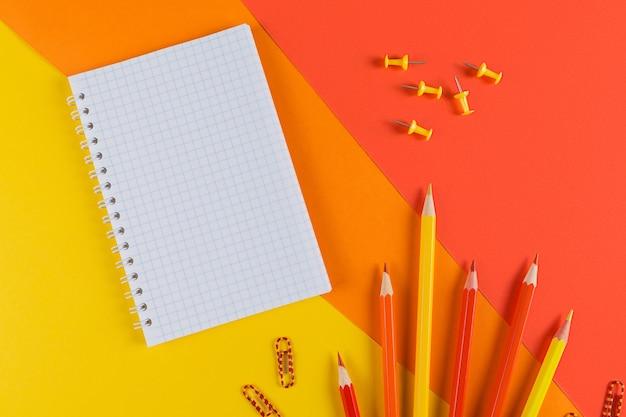 Tavolo scrivania da ufficio giallo e arancione con taccuino in bianco e altre forniture per ufficio. vista dall'alto con copia spazio, piatto laici.