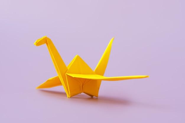 Uccello origami giallo sulla superficie viola