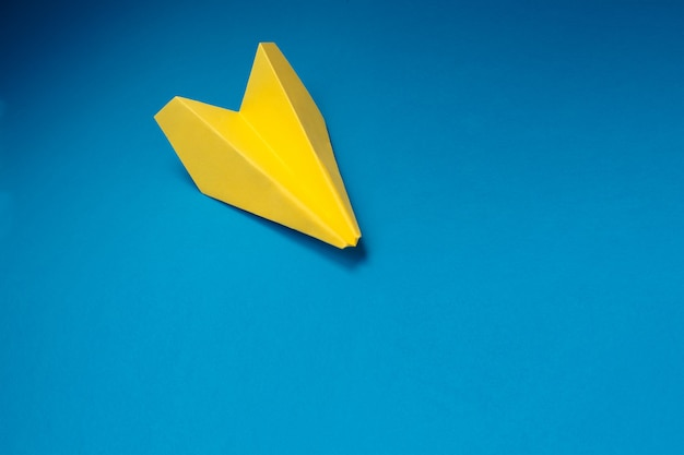 Aereo origami giallo su sfondo blu