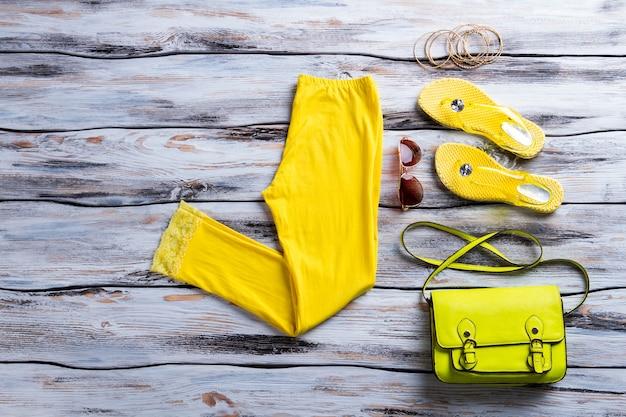 Pantaloni gialli con borsa lime. occhiali da sole da aviatore e bracciali da donna. accessori alla moda sullo scaffale bianco. la migliore merce al prezzo più basso.