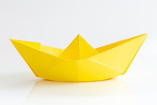 Barca di carta gialla isolata su sfondo bianco