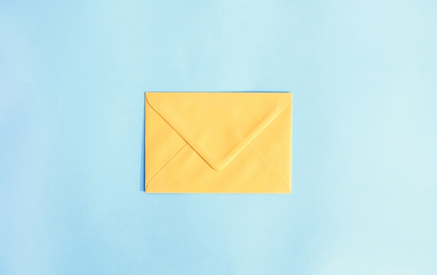 Busta di carta gialla su sfondo azzurro. modello festivo. progettazione di biglietti di auguri. vista dall'alto.