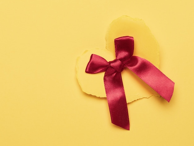 Cuore di carta gialla e fiocco di seta rossa su superficie gialla