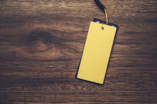 Etichetta di carta gialla sullo sfondo di legno