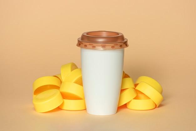 Tappi in plastica gialla con tazza da caffè bianca con coperchio marrone