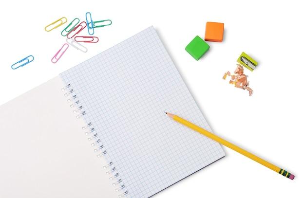 Matita gialla, blocco note a griglia, gomme colorate, temperamatite e graffette isolati su sfondo bianco. cancelleria per la scuola o l'ufficio.