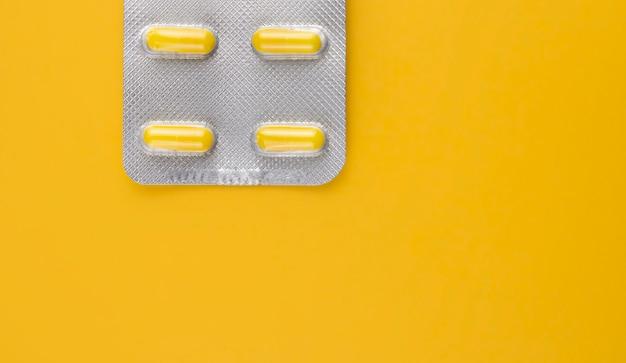 Pillole gialle in un blister su uno spazio giallo della copia della parete.