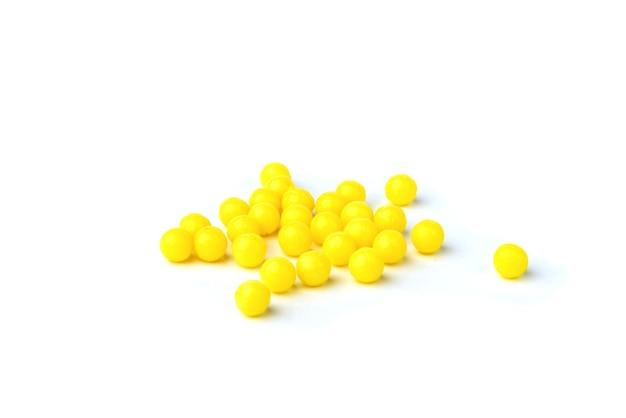Pillole gialle isolate su priorità bassa bianca.