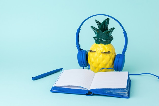Ananas giallo con una penna e un blocco note su una superficie blu. il concetto di digitalizzazione globale.