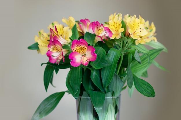 Fiori gialli e rosa in un vaso di vetro