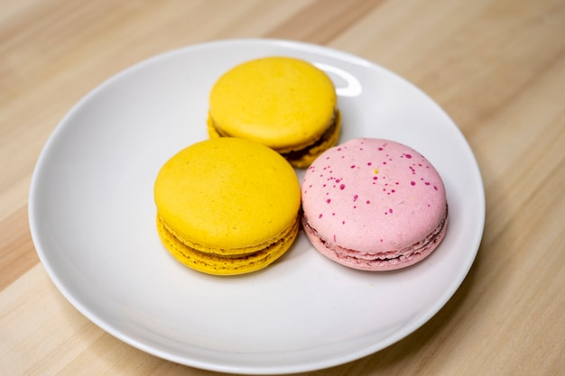 Macarron gialli e rosa su un piatto bianco su un tavolo di legno