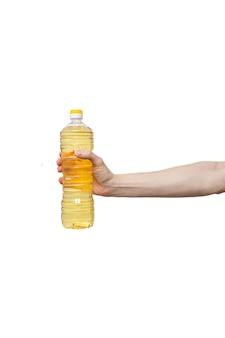 La bottiglia di plastica gialla ha tenuto a disposizione isolato su bianco. uomo che tiene olio vegetale