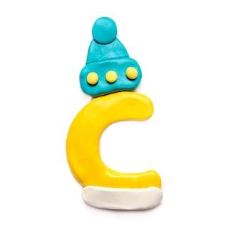 Lettera di plastilina gialla c dell'alfabeto in un berretto invernale blu su sfondo bianco