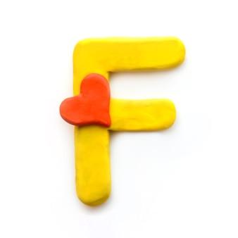 Alfabeto inglese lettera f di plastilina gialla con cuore rosso che significa amore