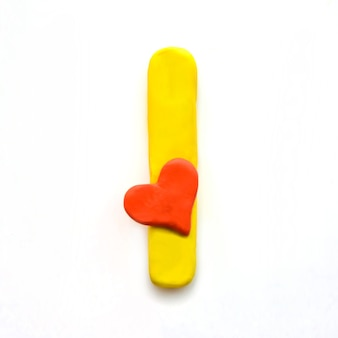 Lettera di plastilina gialla i alfabeto inglese con cuore rosso che significa amore