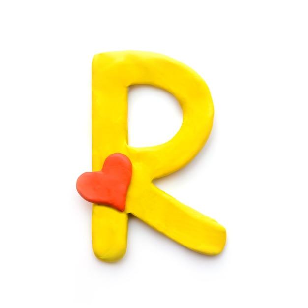 Alfabeto inglese lettera r di plastilina gialla con cuore rosso che significa amore