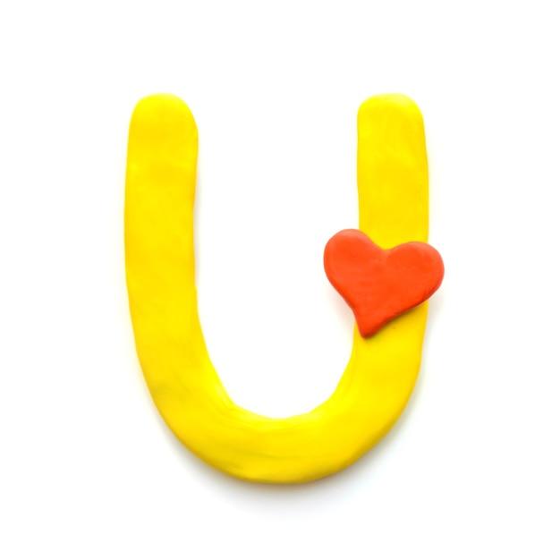 Alfabeto inglese lettera u di plastilina gialla con cuore rosso che significa amore