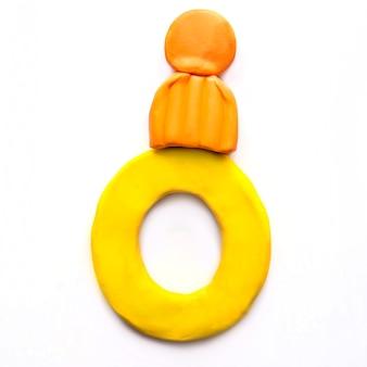 Numero zero di plastilina gialla 0 in protezione invernale arancione su priorità bassa bianca