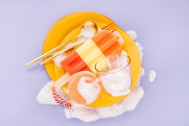 Piatti gialli con cucchiai, forchette e spugna su sfondo di schiuma saponosa. concetto di lavaggio dei piatti. lay piatto, vista dall'alto.