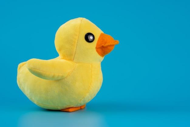 Giocattolo giallo dell'anatra della peluche isolato su priorità bassa blu.