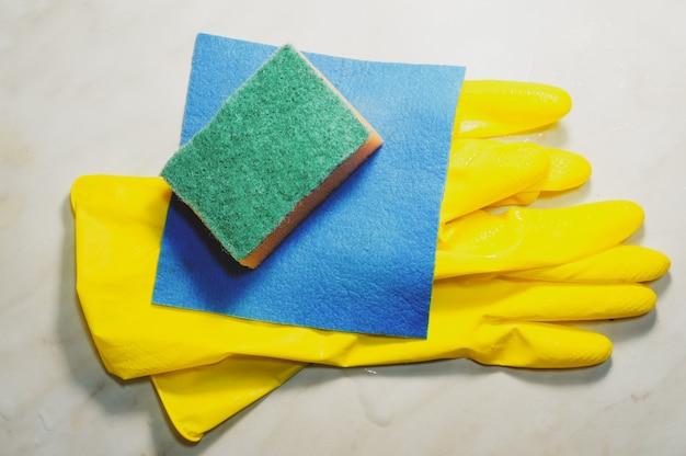Guanti di gomma protettivi gialli, spugna e strofinaccio