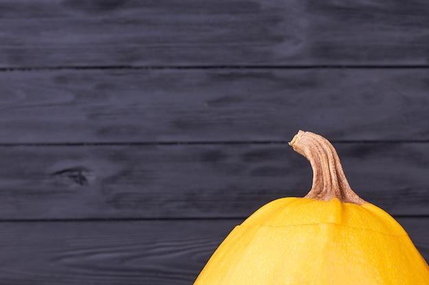 Gambo di zucca gialla su sfondo scuro.