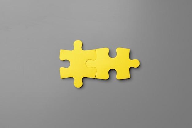 Pezzi di un puzzle giallo su sfondo grigio