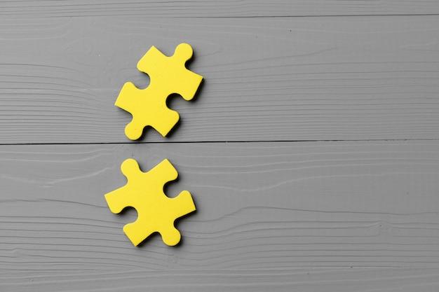 Pezzi di un puzzle giallo sulla superficie grigia