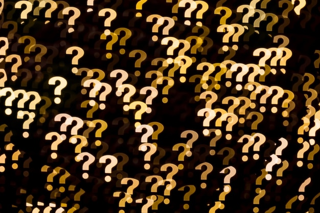 Punti interrogativi gialli bokeh luci sfondo modello astratto su sfondo nero.