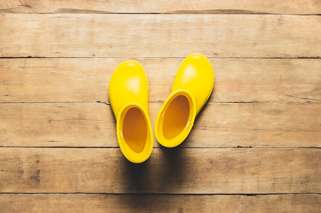 Stivali da pioggia gialli su un fondo di legno. concetto di escursionismo, turismo, campo, montagne, foresta, pioggia.