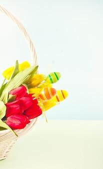 Merce nel carrello dei tulipani gialli e rossi per il giorno di pasqua sui precedenti blu-chiaro. copia spazio.