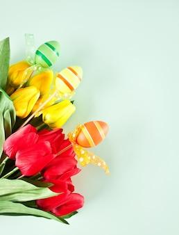 Tulipani gialli e rossi per il giorno di pasqua su sfondo azzurro. copia spazio.